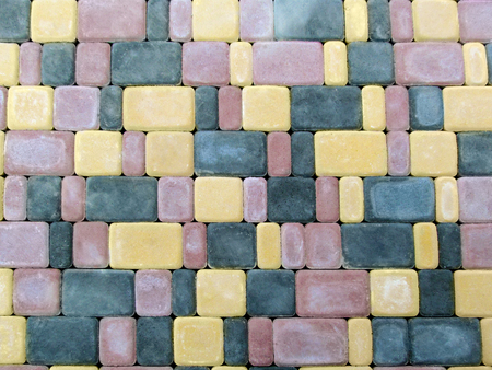 The pattern of the blank surface of the multi-colored paving tiles. The bright texture of red, yellow and black square bricks paving Stok Fotoğraf