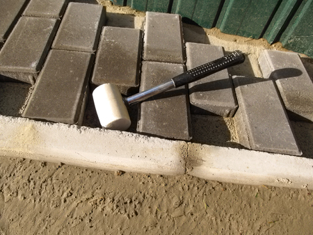 White rubber mallet close up and unfinished work on laying gray paving slabs Brick. Cement-fixed curb, new pavement tiles on the sand and a hammer