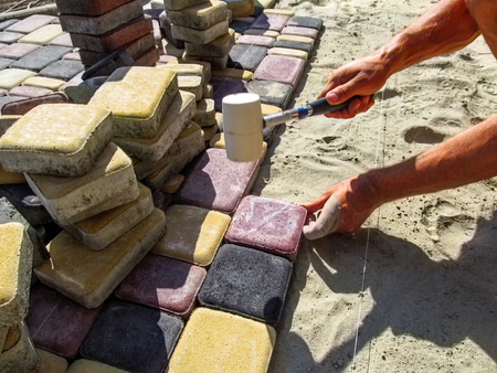 A worker in the process of laying multi-colored paving slabs. A man installs paving bricks on a sand-cement mixture using a rubber mallet
