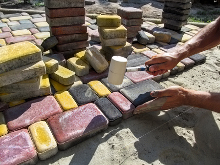 A man, performing work on laying paving slabs, knocks on bright multicolored tiles with a rubber mallet. Male hands with a rubber hammer against the background of colored paving tiles