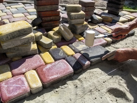 Unfinished work on laying paving slabs on a dry sand-cement mix using a rubber hammer and cord. Male workers hands hammering on the bright tiles Old Town in sunny summer day