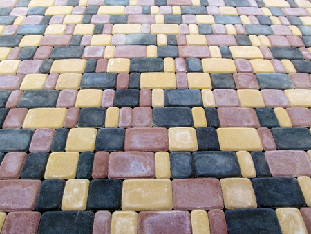 The texture of three-color paving slabs Old Town, top view. A chaotic pattern of red, black and yellow rectangular bricks