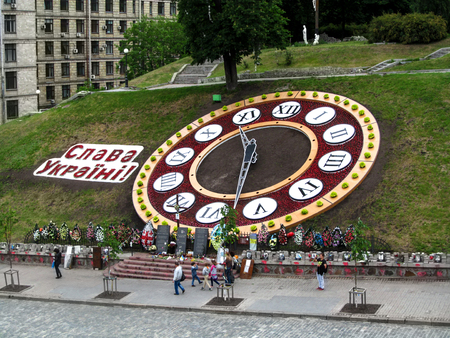 Ukraine, Kiev - May 30,2015: Flower clock with the inscription Glory to Ukraine! on Maidan Nezalezhnosti. Portraits of the Heroes of Heaven Hundreds and remembrance wreaths near a large Flower clock