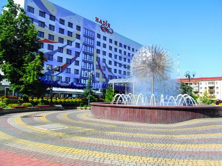 Ukraine, Ivano-Frankivsk - June 05, 2015: Fountain on the Nezalezhnosti Street near Nadiya Hotel in Ivano-Frankivsk. Beautiful ball-shaped Dandelion fountain in the square on a sunny summer day