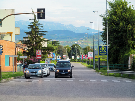 Italy, Verona - August 12, 2016: Cityscape with views of the Alps mountains in the suburbs of Verona. Modern city street with cars on the highway and blue mountains on the horizon Editöryel