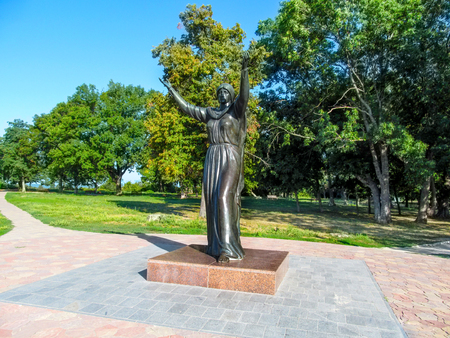 Ukraine, Putyvl - August 18, 2018: Monument to Princess Efrosinya Yaroslavna in Putivl. Bronze female sculpture raised her hands to the sky against the backdrop of autumn nature