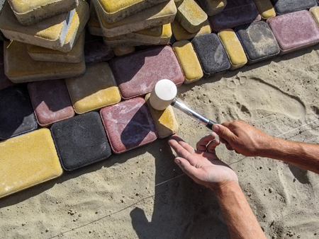 Mens hands with a rubber mallet hit the bright colored pavement tiles. The process of laying paving tiles Old Town, the workplace of the builder Stok Fotoğraf