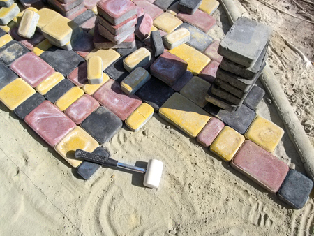 Unfinished paving slabs - the workplace. Piles of beautiful red, yellow and black paving slabs lie on top of a dry sand-cement mix and a rubber mallet lies next to it