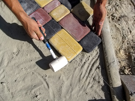 Beautiful construction background for laying paving tiles with copy space. The male hands of the worker install colored paving bricks on the dry sand-cement mix using a rubber mallet