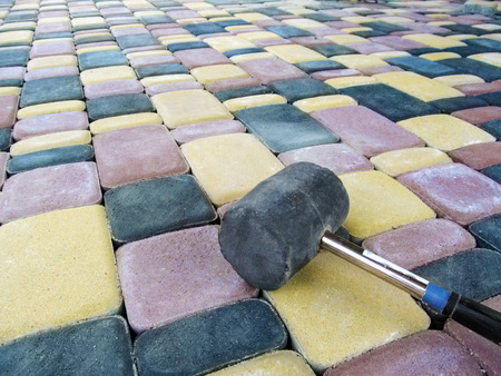 Black rubber mallet lies on the surface of colored paving slabs, close-up. Bright construction background with copy space, paving tile laying concept Stok Fotoğraf