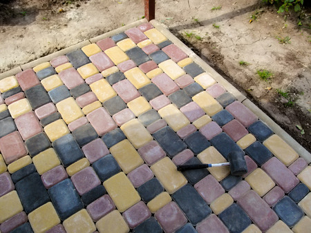 Finished paving area, professional work. Colored bright pavement tiles bordered with a curb and a rubber mallet lies on its surface