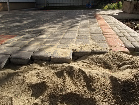 Unfinished laying of gray and red paving slabs. Paving slabs are laid on the sand, side view Stok Fotoğraf