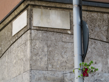 Street corner with granite empty sign-plates and a single plant in a flowerpot hanging on a pipe. Creative simple minimalist background with copy space, beautiful stone walls of a building outdoors Stok Fotoğraf
