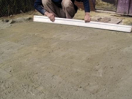A man smooths the surface of a dry sand-cement mixture on the ground using a plastering rule. Creative background with copy space, construction and repair concept