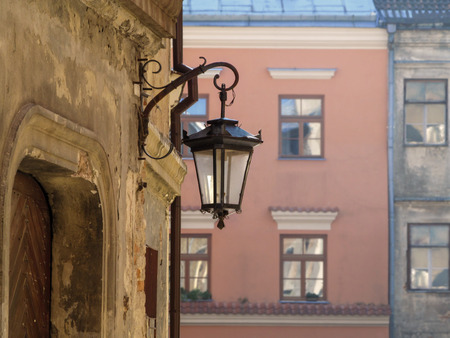 The vintage lantern hangs on the dilapidated wall of an old building on a city street in Lublin (Poland). Beautiful vintage picture of suburb or countryside with copy space