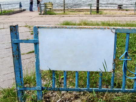 A metal fence with shabby paint and an empty white sign on the embankment, where people fish. Template with copy space - water, embankment, two people and a blank information pointer close-up