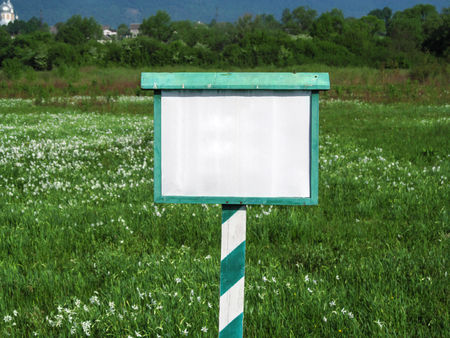 Blank white and green signage close-up against the background of a blooming valley in summer. Simple minimalist template with copy space, nature conservation concept