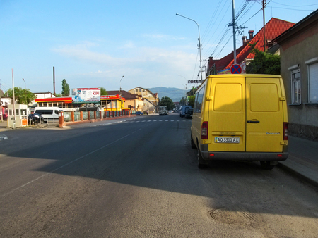 Ukraine, Khust - May 1, 2018: Ivan Franko Street in Khust on a summer morning. Provincial street without people and with transport in a small Transcarpathian mountain town