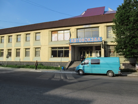 Ukraine, Khust - May 1, 2018: Poor old building bus station in Khust. Blue van stands on city street, it is parked near the porch of the bus station