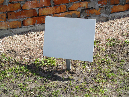 Blank information board sticks out of the ground against a brick wall. White empty rectangular pointer, background with copy space