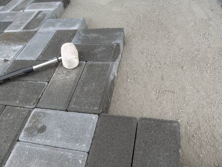 A white rubber mallet lies on the surface of a gray brick paving slab. Beautiful building background with copy space, landscaping concept of sidewalks and courtyards