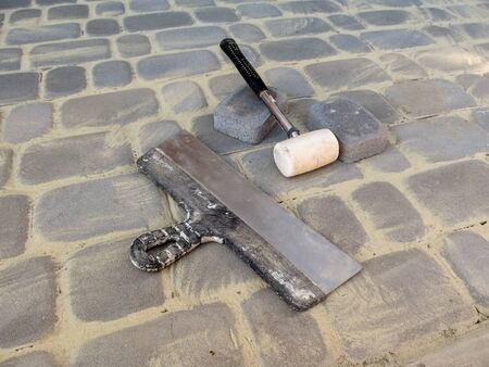 A large putty knife, a white rubber mallet and two bricks lie on the surface of the new paving slabs. The concept of laying paving stones, the result of work