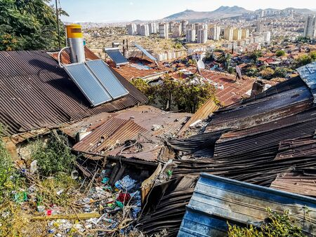 Solar panels and satellite dishes are installed on ancient tiled roofs in the slums of Ankara, Turkey. Garbage and old roofs of huts against the background of a panorama of a modern Turkish city