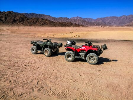 Two ATVs against the backdrop of mountains in the South Sinai Desert near Sharm El Sheikh (Egypt). Red and black quadricycles are standing on the sand, the concept of a tourist excursion on quads