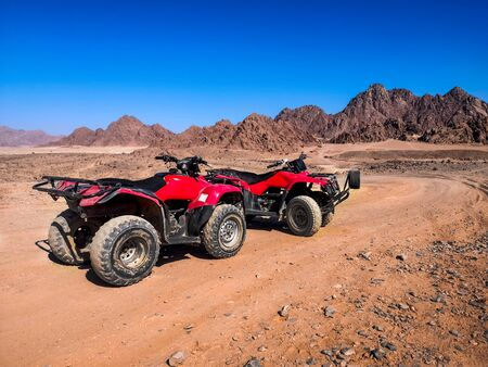 Two red quads stand near the mountains in the South Sinai desert near Sharm El Sheikh (Egypt). ATV safari concept, active leisure for tourists in desert, background with copy space