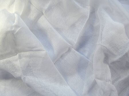 Medical gauze lies carelessly with folds on a white surface. Clean blank white mesh fabric pattern Stockfoto