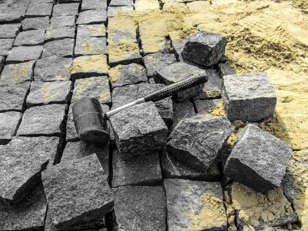 Laying granite paving stones - building background with copy space. A black rubber mallet lies among gray rectangular blocks of natural stone on the background of yellow sand Foto de archivo