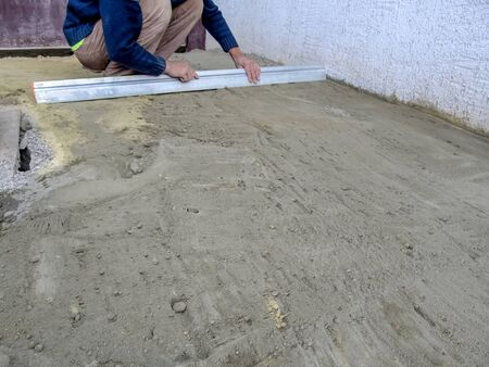 A man smoothes a construction site with a screed tool for laying paving slabs. The builder levels the dry sand-cement mortar on the surface of the ground with the long aluminum ruler, outdoors Stock Photo