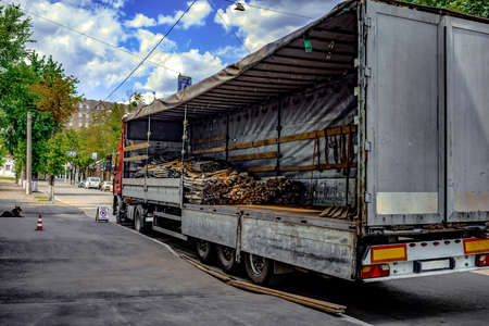 Loading metal rods and cables into cargo wagon of the truck on a city street. Semi-empty cargo box of the lorry, rear side view Stock fotó