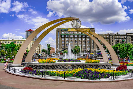 Kharkiv, Ukraine - July 20, 2020: A sculpture with a symbolic globe and a fountain surrounded by multi-colored flower beds at the Pryvokzalna Square in Kharkov. Bright cityscape on a sunny summer day