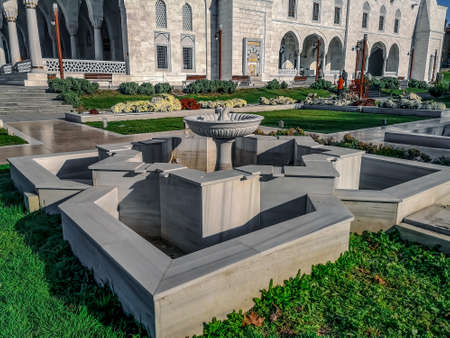 Turkey, Ankara - October 23, 2019: Garden with white marble fountains near Kocatepe Mosque in Ankara. Amazing landscaping in the courtyard of the mosque with flower beds and green grass on the lawn Editoriali