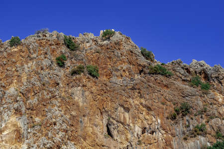Stone cliff with the ruins of the walls of the Alanya (Turkey) at the top. Brown-orange rock with green trees against blue sky. Natural background with copy space Stok Fotoğraf