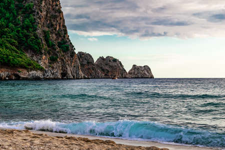 Ship against the backdrop of four rocks in the turquoise water of the Mediterranean Sea in Alanya (Turkey). Seascape with waves crashing on the shore on a summer cloudy day - view from Cleopatra beach