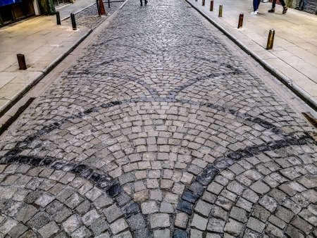 The road is paved with natural granite stone with an arched pattern. Laying paving slabs in the old city streets. Background with copy space