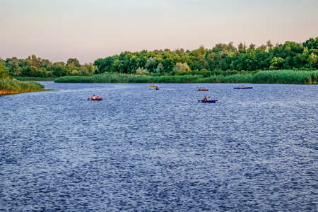 Group of kayaks on the blue water surface of the Konka River on the background of a green wooded coast in Kherson (Ukraine). Sports and entertainment hobbies concept. Summer background with copy space