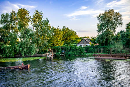 View from the water to a settlement on the coast of the Konka River in Kherson (Ukraine). Country house among summer greenery and a private pier in a swampy reservoir Stockfoto