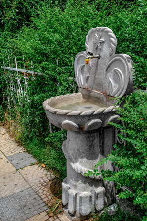 Shkoder, Albania - June 21, 2021: Stone water tap with bowl near Ebu Beker Mosque on Rruga Teuta street in Shkodra. Decorative drinking fountain on the background of a green bush in the park