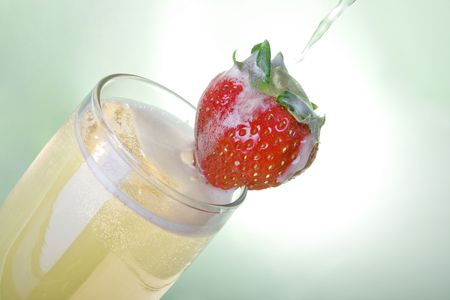 Pouring champagne with strawberry over light green background