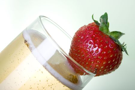 Champagne with Strawberry over light green background photo