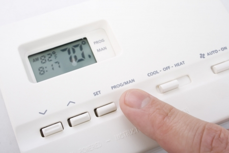 70: Closeup shot of male hand adjusting thermostat to 70 degrees Stock Photo
