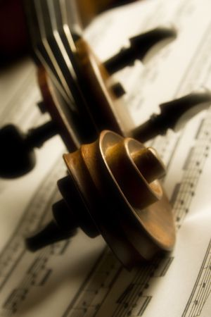 Shot of violin head over partiture, soft focus throughout the entire image gives it a