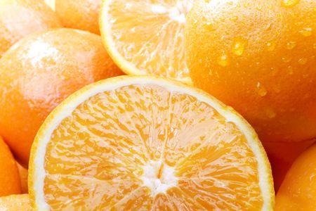 Studio shot of group of oranges, some sliced in half