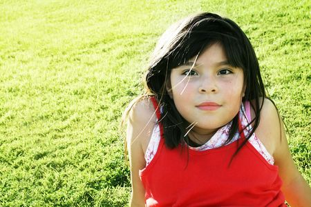 Cute mixed race girl sitting on grass with relaxed look photo
