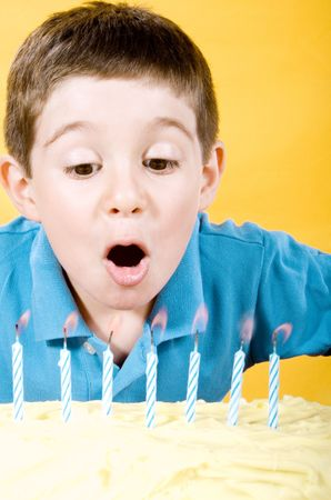 Stock photo of boy blowing candles on cake over yellow background