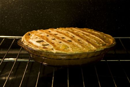 Stock photo of pie in the oven, focus on foreground