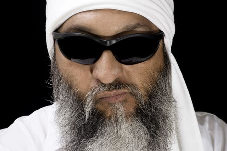 Stock image of Arabic man with long beard wearing turban and sunglasses over dark background